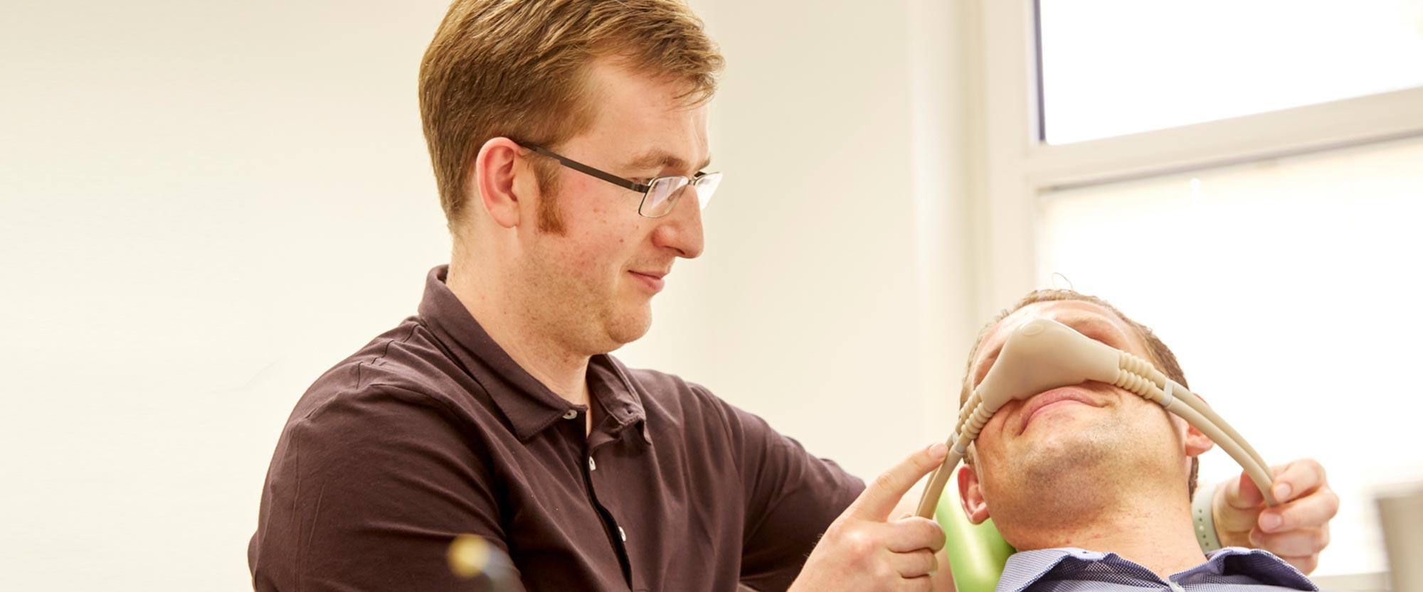Zahnarzt Lennard Bertram stülpt Patienten Nasenmaske über für eine schonende Anästhesie