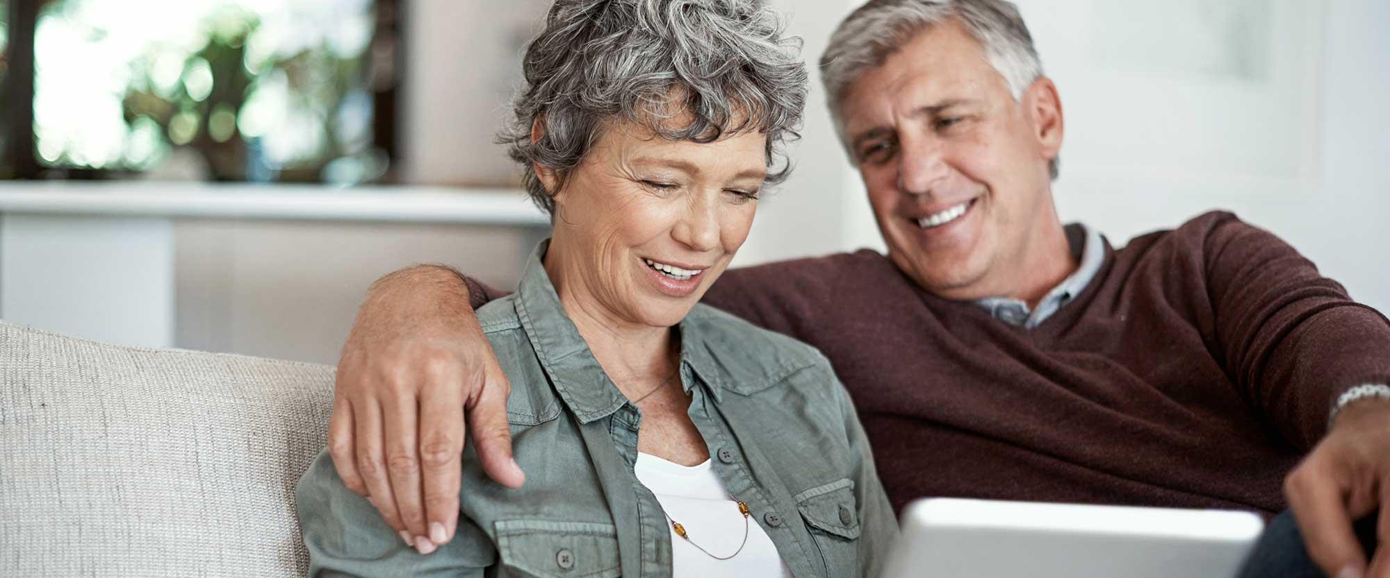 Mann und Frau informieren sich über Implantate und lächeln