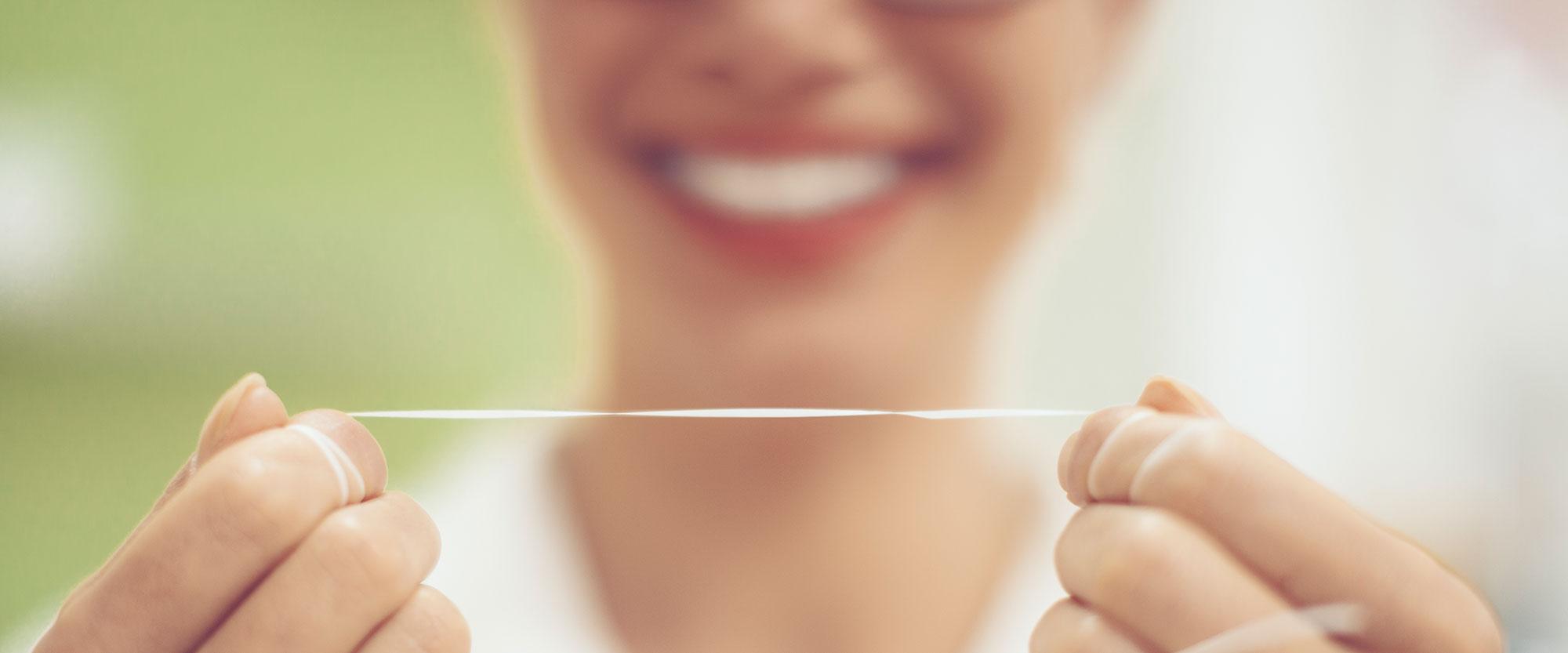 Junge Frau hält Zahnseide in der Hand und lächelt