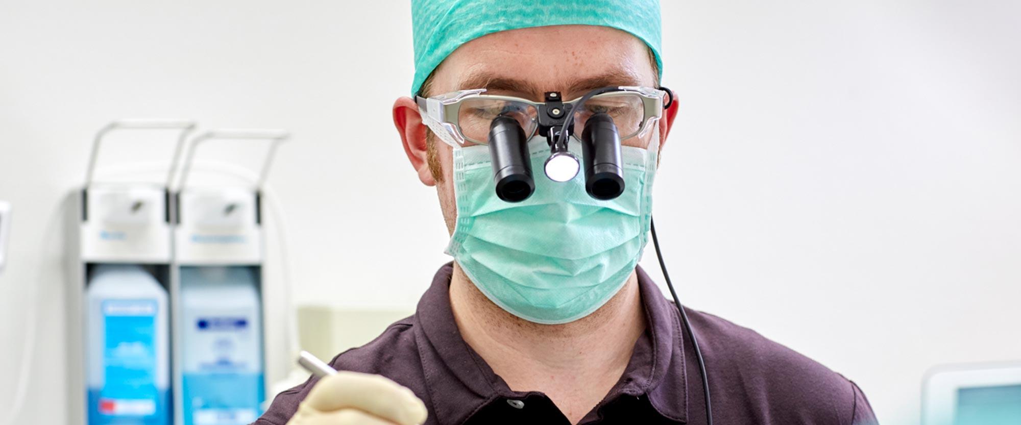 Zahnarzt Lennard Bertram mit Lupe beim Knochenaufbau