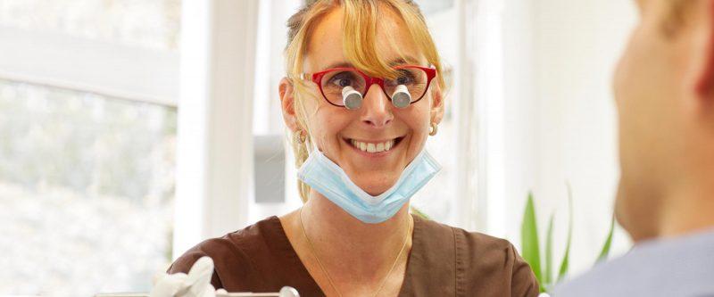 Ester Hoekstra lächelt Patient an, den Sie beim Zahnerhalt unterstützt