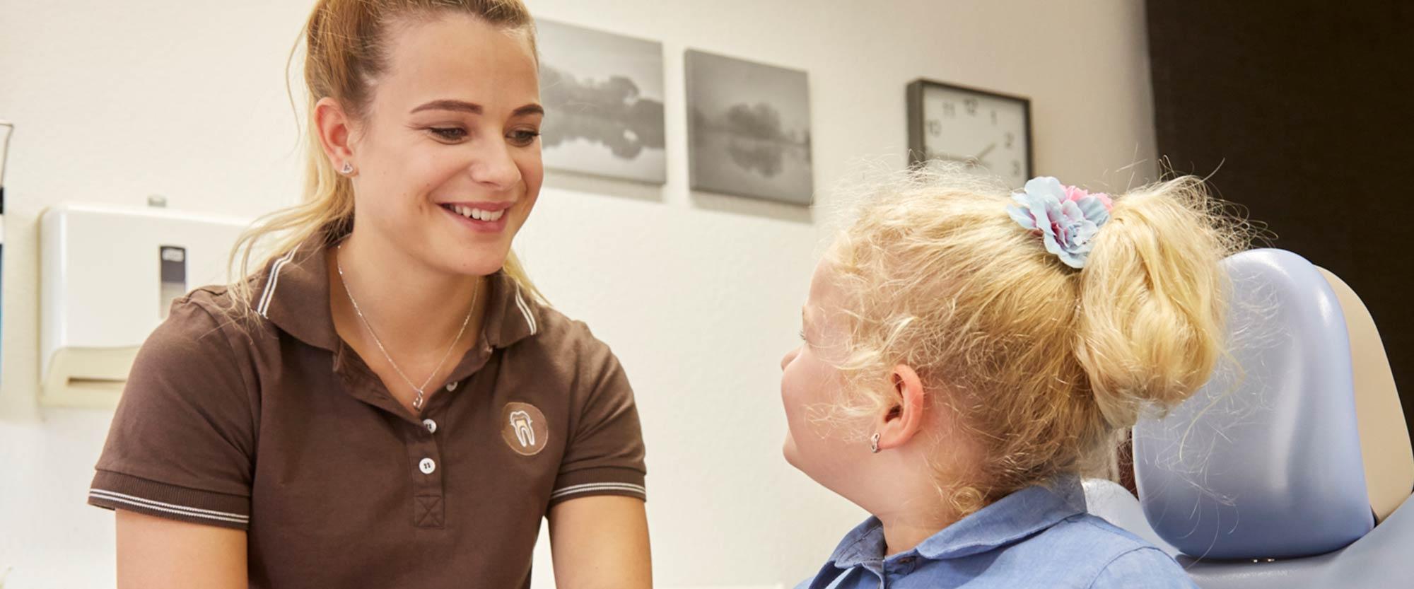 Selina Schimmank lächelt Mädchen an, dem sie Tipps für das Zähneputzen gegeben hat.