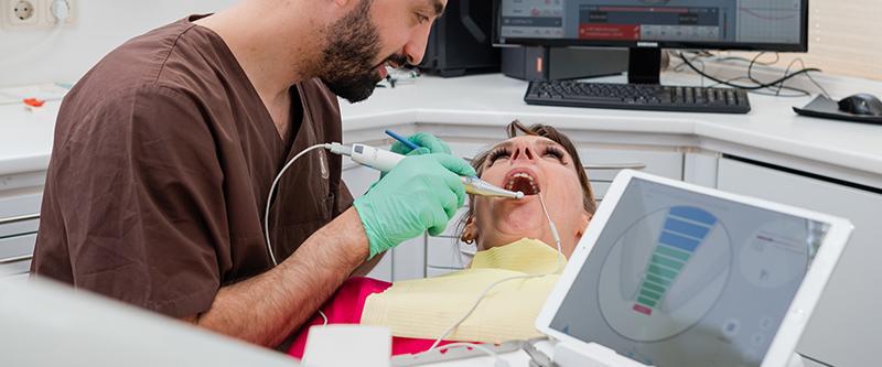 Frau liegt auf einem Zaahnarztstuhl und ein Zahnarzt führt einen Zahnwurzelmessung durch.